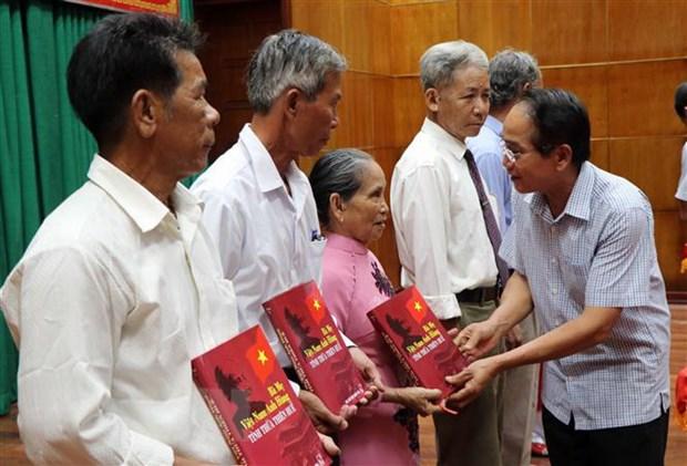 Phó Bí thư Thường trực Tỉnh ủy Thừa Thiên-Huế Bùi Thanh Hà tặng sách cho thân nhân các Mẹ Việt Nam Anh hùng được ghi danh và ghi công trong cuốn sách. (Ảnh: Đỗ Trưởng/TTXVN)