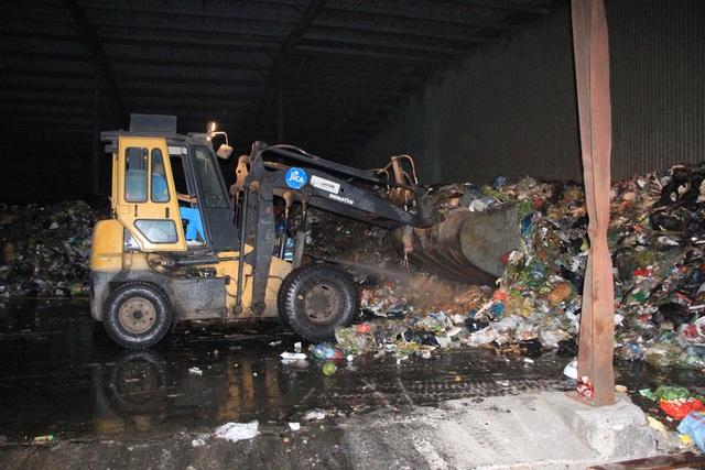 Sau khi xe chở rác tới, máy ủi sẽ vun những đống rác cao để phủ bạt.