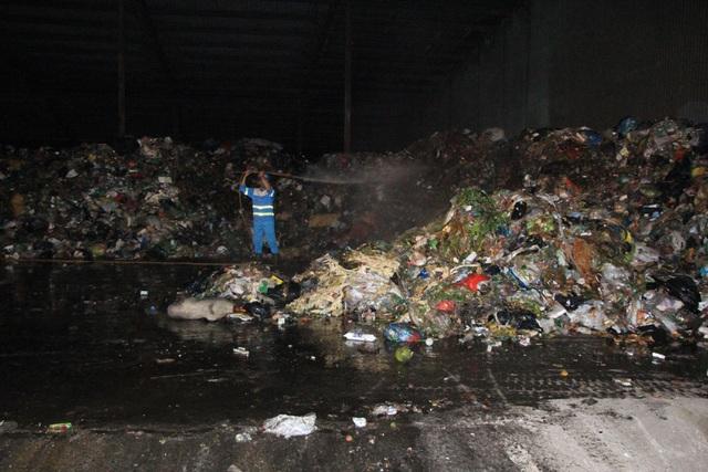 Công nhân phun thuốc khử mùi, diệt ruồi trên bề mặt đống rác.