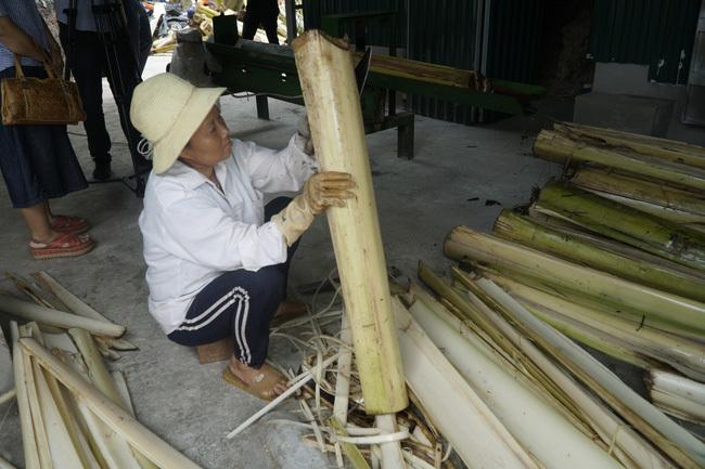 Công nhân bóc tách bẹ chuối trước khi đưa vào máy chẻ, ép thành sợi.