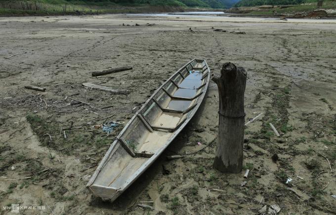 Một chiếc thuyền của người dân cột vào gốc cây dưới lòng hồ cạn.