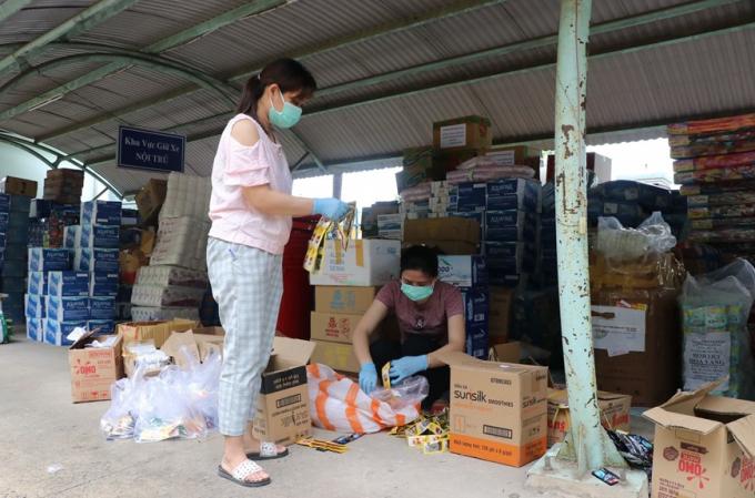 Các điều dưỡng của Trung tâm y tế huyện Hòa Vang có thêm nhiệm vụ phân chia đồ dùng, nhu yếu phẩm. (Ảnh: Quốc Dũng/TTXVN)