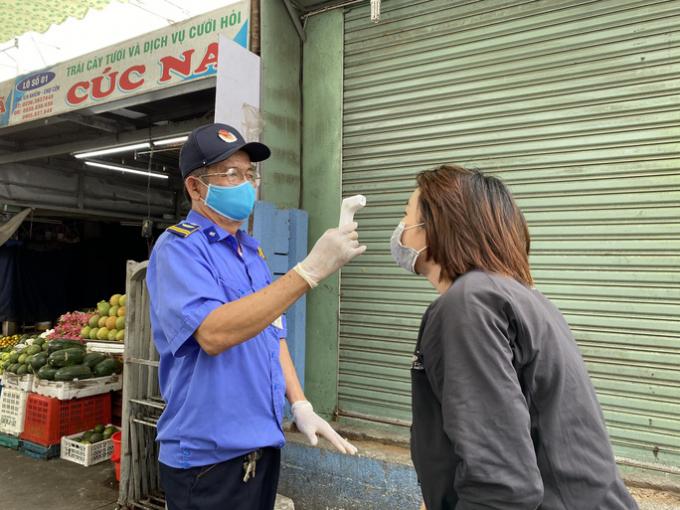 Lực lượng bảo vệ túc trực để đo thân nhiệt mỗi người vào trong.