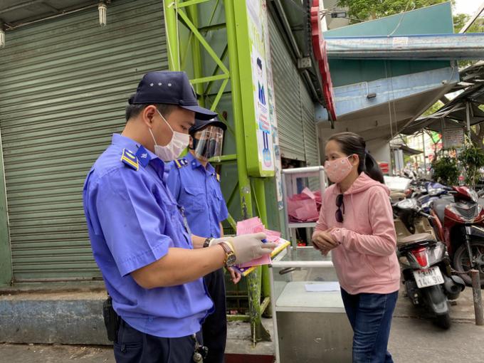 Trong ngày 12-8, người dân vào chợ phải mang theo phiếu màu hồnglà quy định cho ngày chẵn.Người dân vào chợ Cồn - Đà Nẵng được kiểm tra qua chốt bảo vệ ở cổng chính.