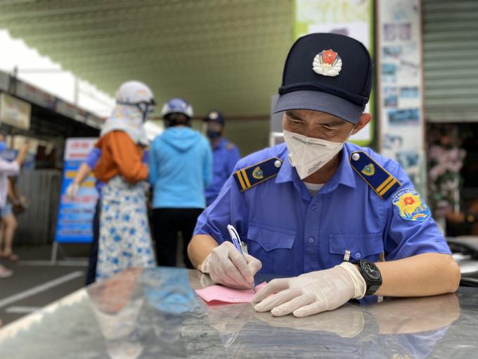 Bảo vệ chợ Cồn điền thông tin vào phiếu giúp người dân trước khi vào chợ.