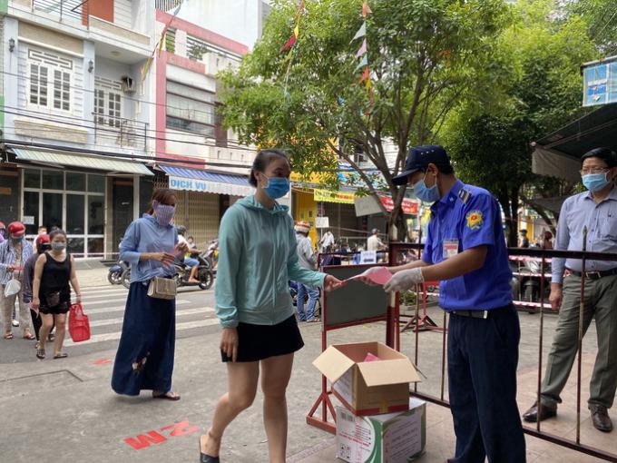 Tại chợ Đống Đa, người dân cũng xếp hàng chờ kiểm tra phiếu trước khi vào.