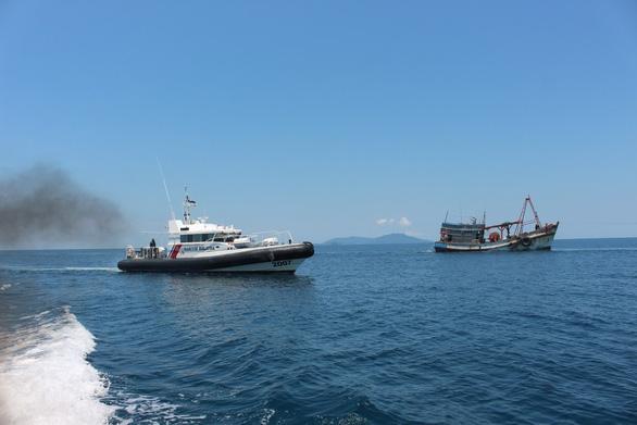 Tàu tuần tra của Malaysia áp tải tàu cá Việt Nam (phải) vào bờ - Ảnh: MMEA