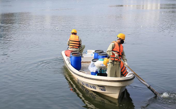 Công nhân thoát nước phun rải hóa chất ở hồ Hoàng Cầu tháng 9/2016. Ảnh: Thanh Hiếu.