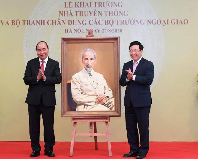 Thủ tướng Nguyễn Xuân Phúc và Phó thủ tướng - Bộ trưởng Ngoại giao Phạm Bình Minh bên bức tranh chân dung Chủ tịch Hồ Chí Minh (họa sĩ Lê Anh Vân)ẢNH: BTC