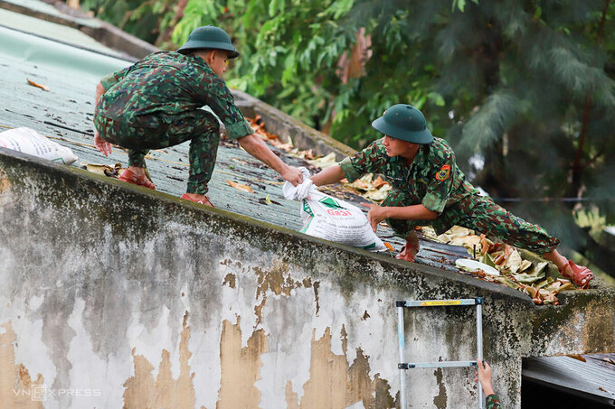 Chiến sĩ Đồn Biên phòng Phú Lộc giúp dân chằng chống lại nhà cửa. Ảnh: Nguyễn Đông.