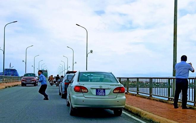 Đoàn xe biển xanh dừng lại trên cầu Nhật Lê 1.