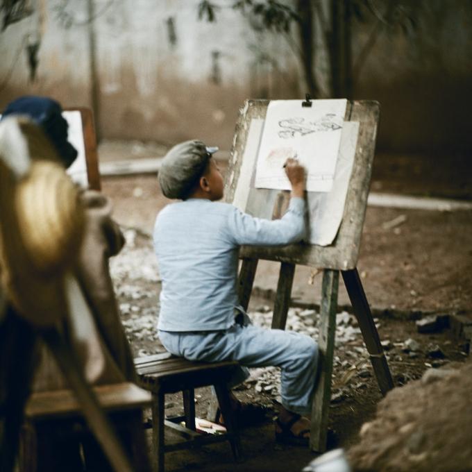 Khoảnh khắc em bé mặc bộ đồ màu xanh, đội mũ nồi trong giờ học vẽ ngoài trời được chụp năm 1968.