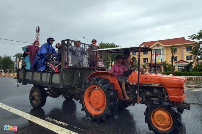 Xe máy cày kéo theo rơ móc để chở người và xe máy qua khu vực ngập sâu trên quốc lộ 1A. Mỗi lượt người và xe với giá 100.000 đồng.
