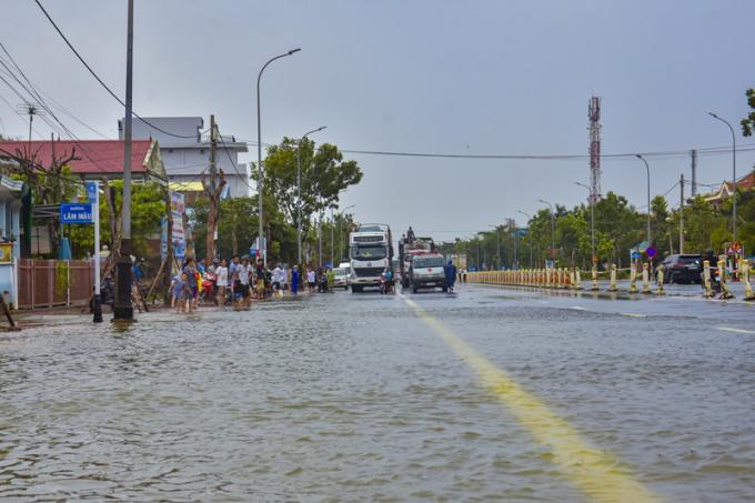 Nhiều phương tiện và người dân vẫn chờ nước tại quốc lộ này rút để đi qua.