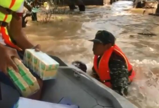 Người đàn ông nhảy khỏi thuyền bế em bé giữa dòng nước lũ.