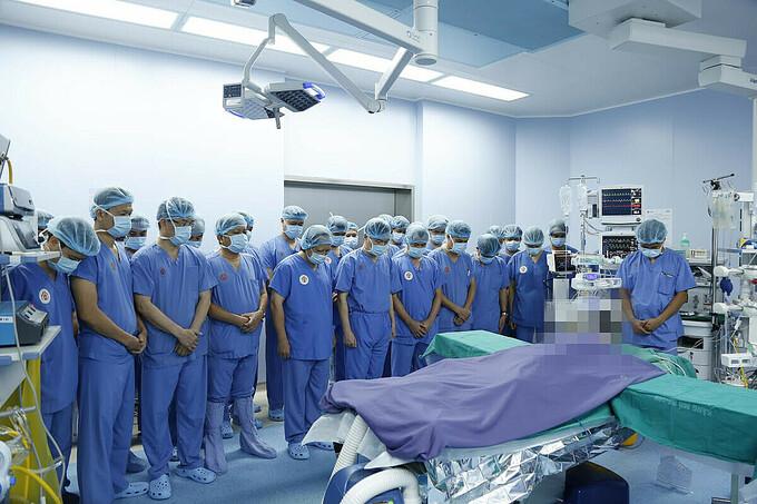 Các bác sĩ cúi đầu mặc niệm người hiến tạng chết não, trước khi phẫu thuật nhận và ghép tạng, hồi tháng 9.