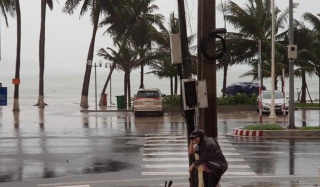 Một người đi đường phải nấp sau cột điện để tránh gió mạnh.