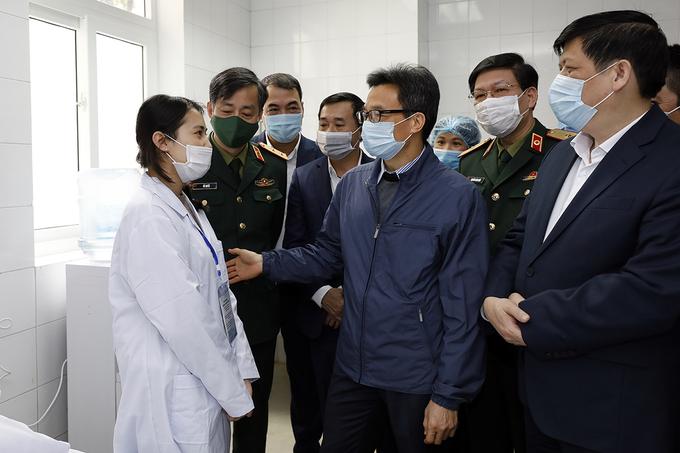 Phó thủ tướng Vũ Đức Đam động viên một trong ba tình nguyện viên đầu tiên tiêm thử nghiệm vaccine Covid-19 do Việt Nam sản xuất. Ảnh: VGP