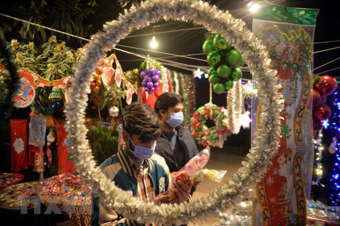 Người dân chọn mua đồ trang trí Giáng sinh tại Peshawar, Pakistan. (Ảnh: THX/TTXVN)