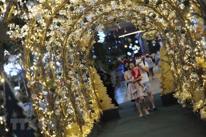 Người dân chụp ảnh bên đèn trang trí Giáng sinh tại Singapore. (Ảnh: THX/TTXVN)