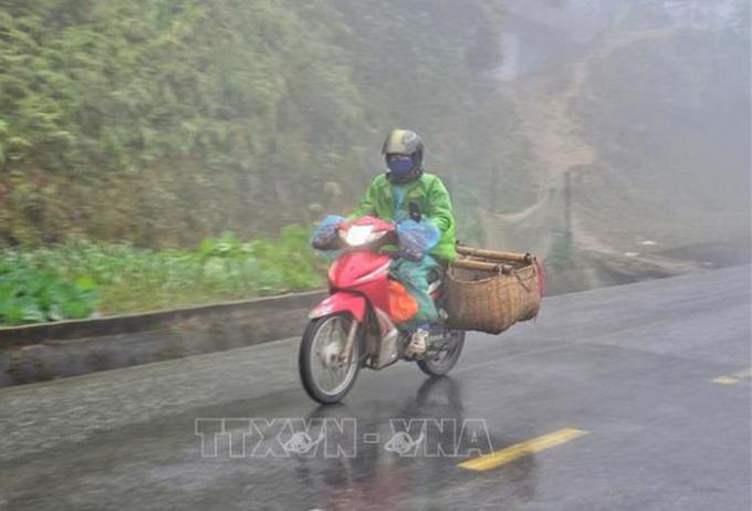 Người dân đi xe máy vận chuyển hàng hóa trong sương sớm, giá lạnh trên đỉnh đèo Pha Đin (Điện Biên). Ảnh: Xuân Tiến-TTXVN