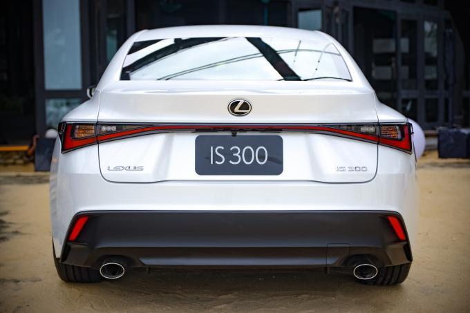 """Lexus IS 2021 cuốn hút với """"gương mặt"""" cực kỳ ấn tượng với trung tâm là lưới tản nhiệt mang biểu tượng thương hiệu hình con suốt cực lớn với cấu trúc đa diện biến ảo theo ánh sáng và các góc nhìn. Hai bên hông xe nở rộng theo phong cách coupe kết hợp các đường cong mềm mại với vẻ đường bệ, chắc chắn. Và nhìn từ phía sau, hai dải đèn LED kéo dài tạo hình duyên dáng – có thể liên tưởng tới một chiếc nơ sang trọng đặc biệt nổi bật khi xe lên đèn."""