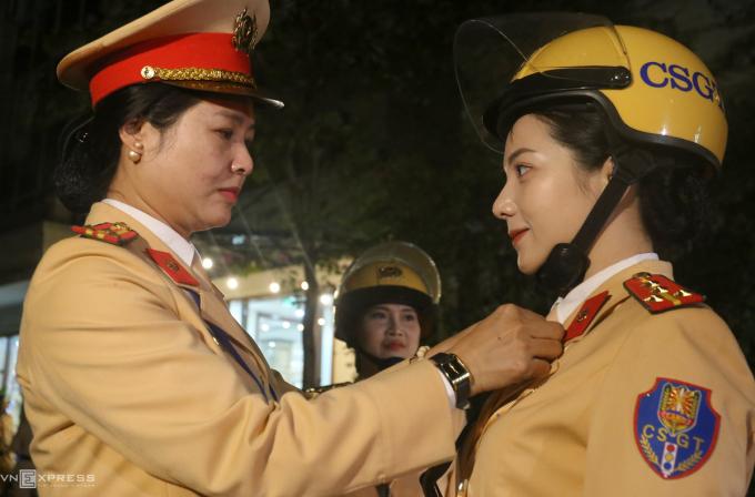 Thượng tá Đặng Thị Lanh, Chủ tịch Hội phụ nữ Cục Cảnh sát chỉnh đốn trang phục cho các nữ cảnh sát vàphátbánh, kẹo, đồ ăn để ăn vào những lúc nghỉ ngơi buổi trưa và tối.