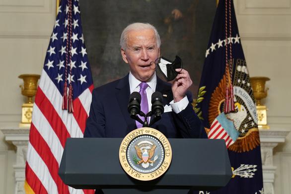 Tổng thống Biden cầm khẩu trang khi phát biểu về cuộc chiến chống dịch COVID-19 tại Nhà Trắng chiều 26-1-2021 - Ảnh: REUTERS