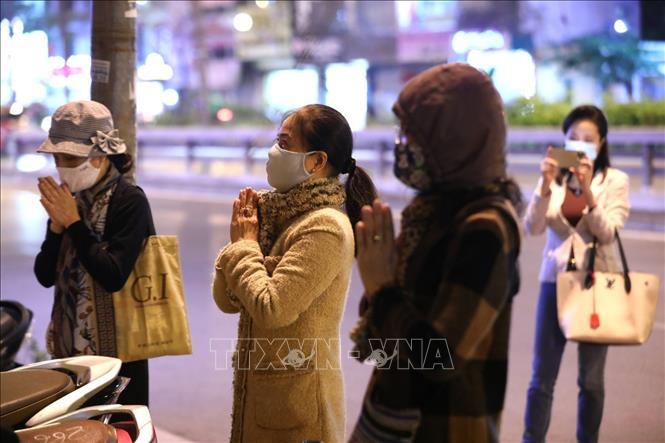 Lác đác vài người tìm đến chắp tay cầu an trước cửa chùa Phúc Khánh tối 25/2 (14/1 âm lịch). Ảnh: Thành Đạt/TTXVN