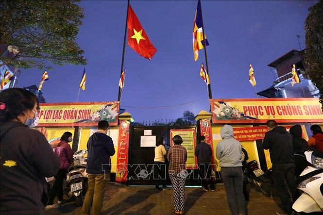 Người dân đứng ngoài chùa Phúc Khánh chắp tay vái vọng cầu bình an. Ảnh: Thành Đạt/TTXVN