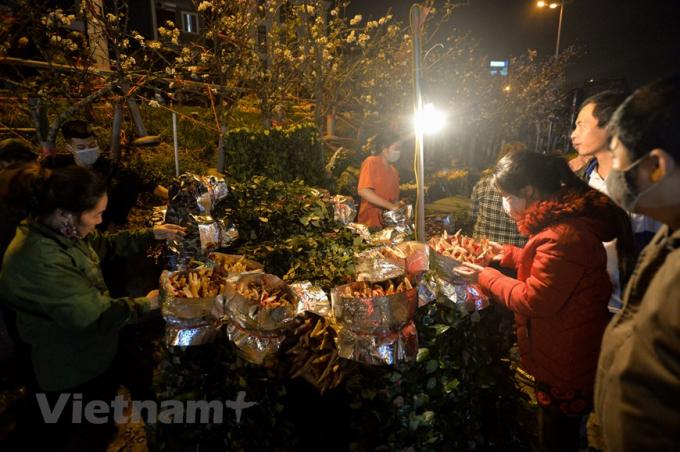 Đây cũng là thời điểm nhiều người dân lựa chọn để đi chợ vì sẽ kiếm được hoa tươi, giá ưng ý. (Ảnh: Minh Sơn/Vietnam+)
