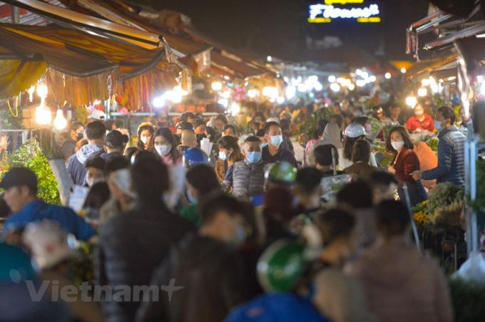 Khác với cảnh ảm đạm, ế hàng năm ngoái, chợ hoa lớn nhất Thủ đô lại tấp nập người mua, kẻ bán khi ngày Quốc tế Phụ nữ 8/3 đang cận kề. (Ảnh: Minh Sơn/Vietnam+)