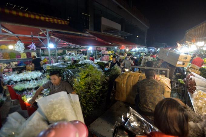 Cảnh các xe chở hàng trăm bông hoa di chuyển từng chút một trong khu chợ đã trở lại. (Ảnh: Minh Sơn/Vietnam+)