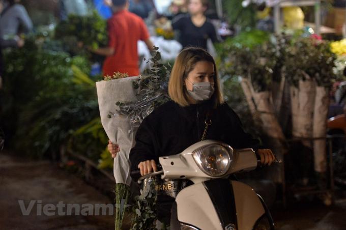 Chợ hoa Quảng An thường sẽ họp vào lúc 9 giờ tối đến nửa đêm. Các tiểu thương sẽ đi mua hoa từ các sạp hàng hoặc kho bán buôn. (Ảnh: Minh Sơn/Vietnam+)