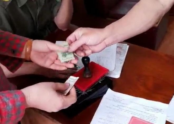 Người phụ nữ đưa 200.000 đồng khi đóng lệ phí làm CCCD gắn chip và được công an trả lại 100.000 đồng. Ảnh cắt từ clip.