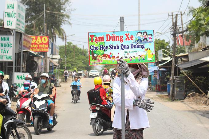 Bà Phượng đứng cầm bảng xin đường cho học sinh di chuyển sang đường trưa ngày 8/4. Ảnh: Diệp Phan.
