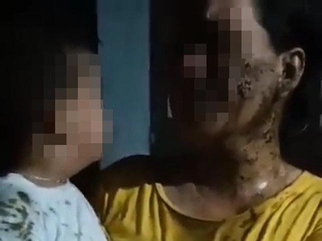 Mẹ con bà C.T.G bị đổ phân bẩn khắp người (ảnh cắt từ clip).