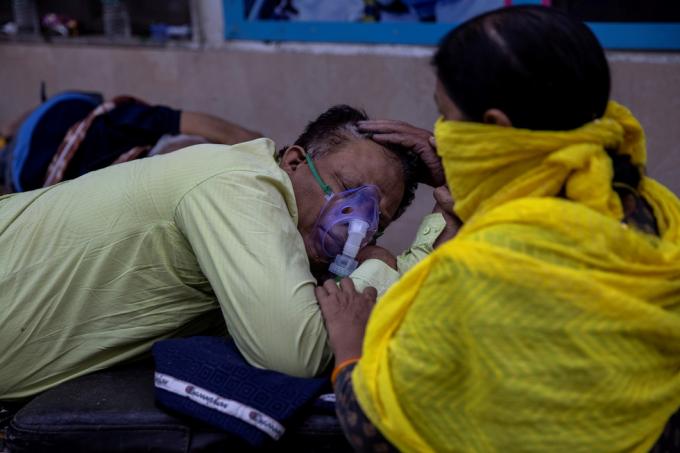 Người phụ nữ chăm sóc cho chồng nhiễm COVID-19 ở hành lang Bệnh viện Guru Teg Bahadur tại thủ đô New Delhi, ngày 23-4.