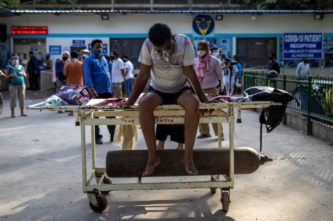 Bệnh nhân với bộ mặt nạ thở oxy và bình oxy ở bên ngoài Bệnh viện Guru Teg Bahadur tại thủ đô New Delhi, ngày 23-4 do chưa có giường điều trị.