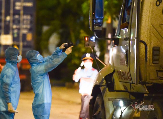 Giữa đêm về sáng, phương tiện vận chuyển hàng vào TP.HCM đông đúc, lực lượng kiểm soát nhanh chóng hướng dẫn các tài xế khai báo y tế, đo thân nhiệt khi vào thành phố