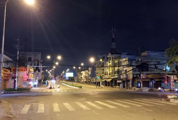 Ngã tư chợ Cầu (nút giao đường Tô Ký-Nguyễn Văn Quá) lúc 22 giờ ngày 30/5, 'cửa ngõ' hướng vào quận Gò Vấp khá vắng vẻ trước giờ giãn cách xã hội. (Ảnh: Tiến Lực/TTXVN)
