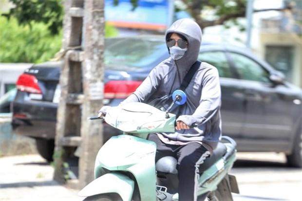 Người dân khi tham gia giao thông giữa nắng nóng. (Ảnh: Tuấn Đức/TTXVN)