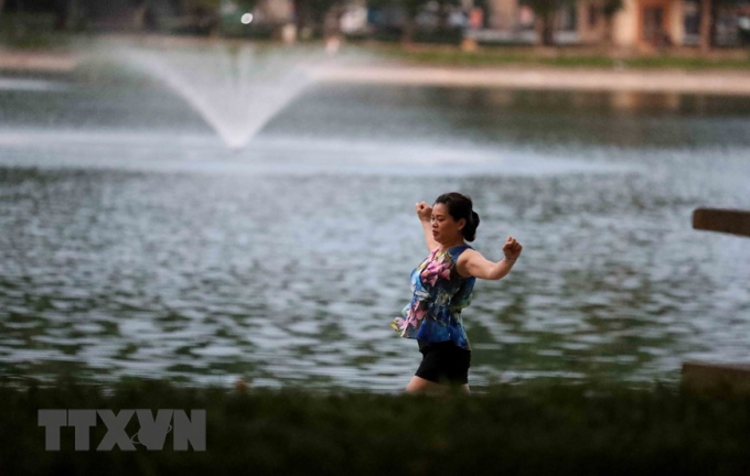 Vượt qua rào chặn để vào tập thể dục tại hồ Thiền Quang lúc 5h sáng 26/7. (Ảnh: Nhật Anh/TTXVN)