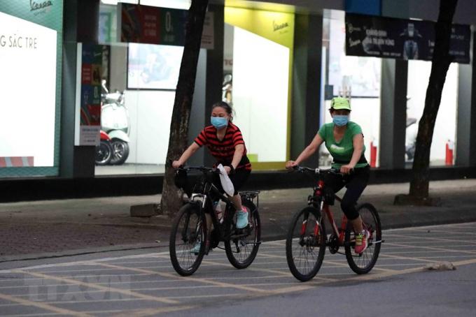 Người dân đạp xe thể dục lúc 5h sáng 26/7 trên đường Lê Duẩn. (Ảnh: Nhật Anh/TTXVN)