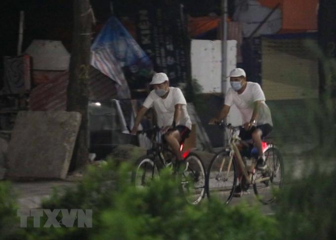 Người dân đạp xe trên đường Lạc Long Quân từ sớm để tránh lực lượng chức năng (ảnh chụp lúc 4h06 phút). (Ảnh: Thanh Tùng/TTXVN)