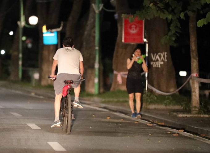 Người dân đạp xe trên đường Thanh Niên từ sớm để tránh lực lượng chức năng (ảnh chụp lúc 4h23 phút). (Ảnh: Thanh Tùng/TTXVN)