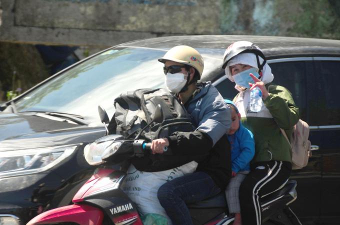 Một cặp vợ chồng người Mông quê ở Tương Dương, tỉnh Nghệ An chạy xe máy từ Bình Dương về quê trưa 27-7