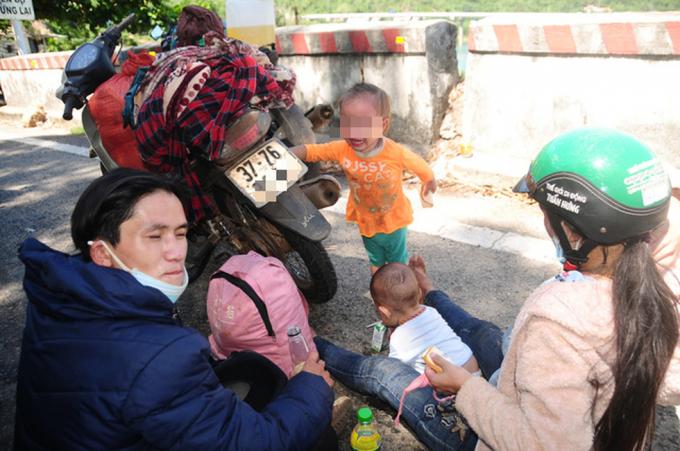 Phút nghỉ ngơi giữa đường trên hành trình về quê của anh Vừ Bá Dũng (Kỳ Sơn, Nghệ An) cùng vợ và hai con nhỏ