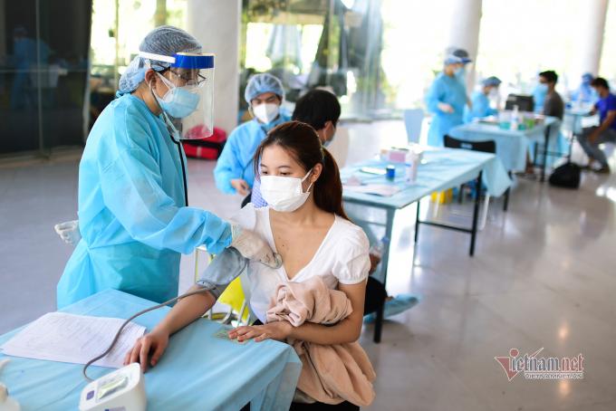 Một cô gái được đo huyết áp trước khi tiêm