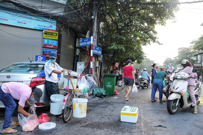 Các tiểu thương và người mua tiếp tục di chuyển xuống đoạn ngã ba Hàng Đậu - Nguyễn Thiệp để mua bán sau khi việc họp chợ khu vực bốt Hàng Đậu bị lực lượng chức năng giải tán. (Ảnh: Thành Đạt/TTXVN)